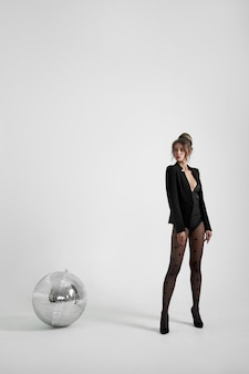 Moda donna sexy su sfondo bianco vicino a palla da discoteca, bel corpo sottile di donna