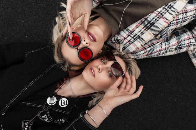Amiche sexy alla moda con belle labbra con capelli biondi in abiti giovanili alla moda in occhiali vintage, vista dall'alto