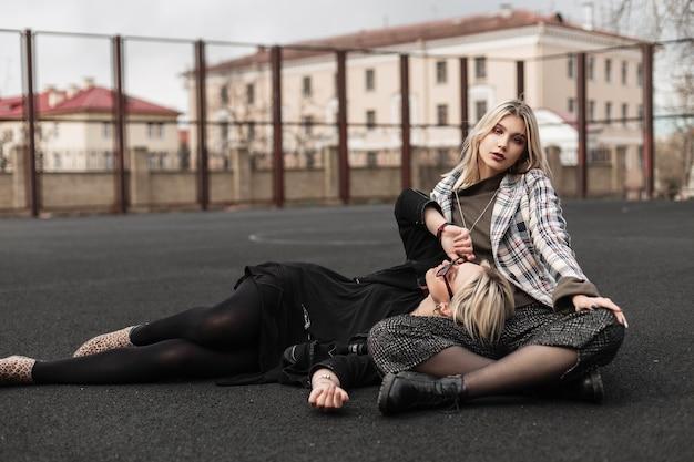 Sorelle gemelle alla moda sexy che riposano sul campo da giuoco su street