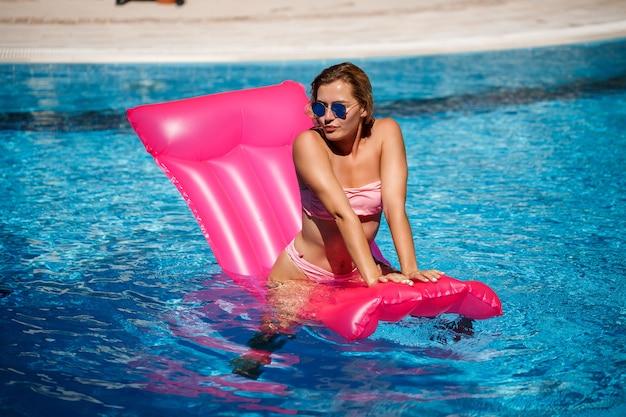 Modello femminile sexy in occhiali da sole che riposa e prende il sole su un materasso in piscina. donna in un costume da bagno bikini rosa che galleggia su un materasso rosa gonfiabile. spf e crema solare