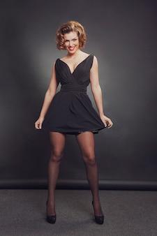 Modello femminile sexy con acconciatura che indossa un abito nero, in posa