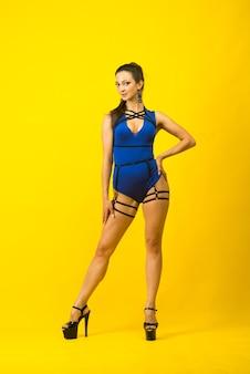 Ballerina sexy del palo femminile che indossa tuta blu e tacchi alti su uno sfondo giallo