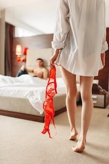 Femmina sexy con reggiseno rosso in mano, coppia imitata