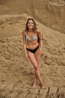 Donna seducente in forma sexy in bikini che si rilassa a prendere il sole da sola sulla spiaggia sabbiosa