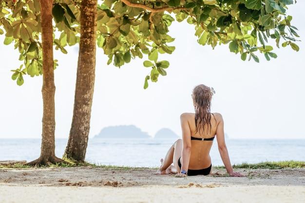 Donna sexy adatta in bikini sulla spiaggia