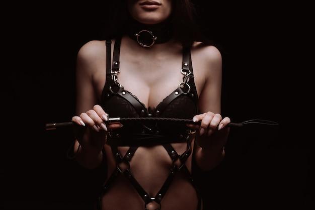 Ragazza sexy in un bel reggiseno nero che gioca con una frusta. il concetto di bdsm