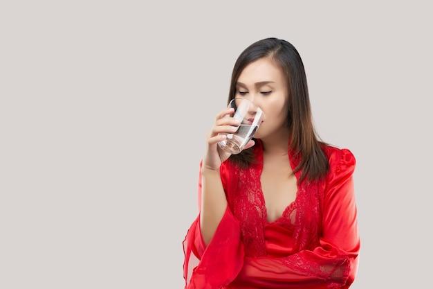 Ragazza sexy che beve un bicchiere d'acqua prima di andare a letto su uno sfondo grigio