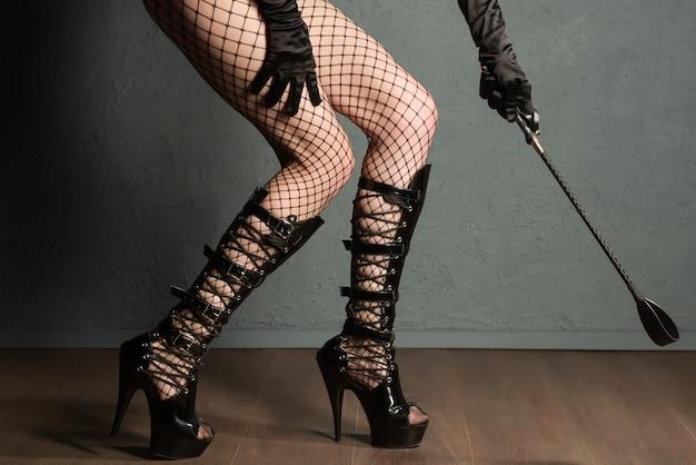 Gambe di ragazza sexy in calze a rete e stivali fetish con tacchi alti con frusta si preparano per la punizione.