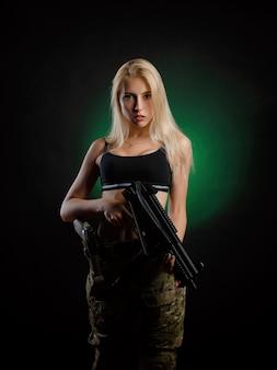 Una ragazza sexy in tuta militare softair posa con un fucile d'assalto su uno sfondo scuro