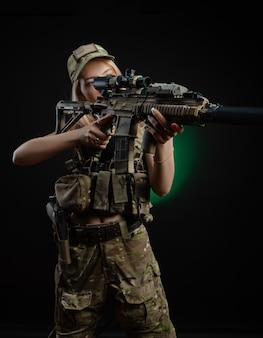 Una ragazza sexy in tuta militare softair posa con una pistola in mano su uno sfondo scuro
