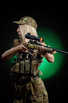 Una ragazza sexy in tuta militare softair posa con un fucile da cecchino su uno sfondo scuro