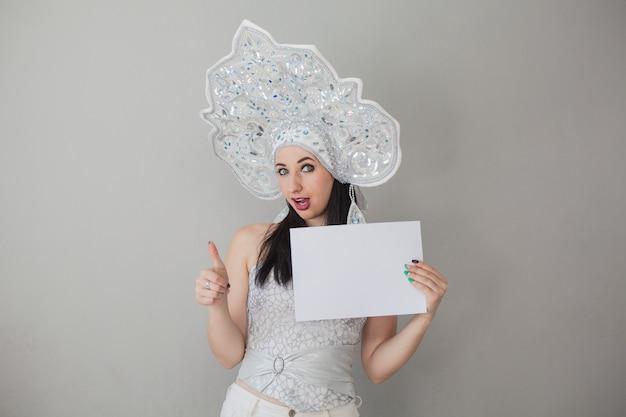 Ragazza sexy nel capodanno russo kokoshnik regina delle nevi con un cartello per le iscrizioni