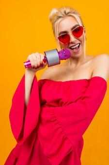 Ragazza sexy in un vestito rosso festeggia un compleanno e canta al karaoke