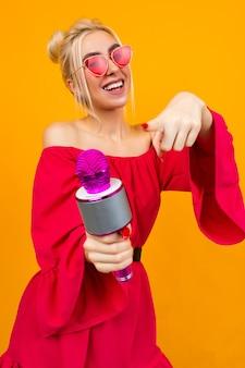 La ragazza sexy in un vestito rosso festeggia un compleanno e canta in karaoke