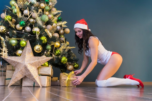 Ragazza sexy in costume da babbo natale aprendo un regalo contro l'albero di natale in camera. la mattina presto dopo natale o capodanno. regali sotto l'albero sul pavimento