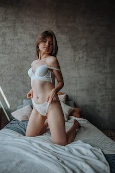 Ragazza sexy seduta sul letto in lingerie bianca