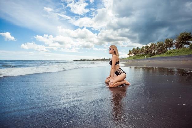 Ragazza sexy in costume da bagno si siede sulla spiaggia con sabbia nera