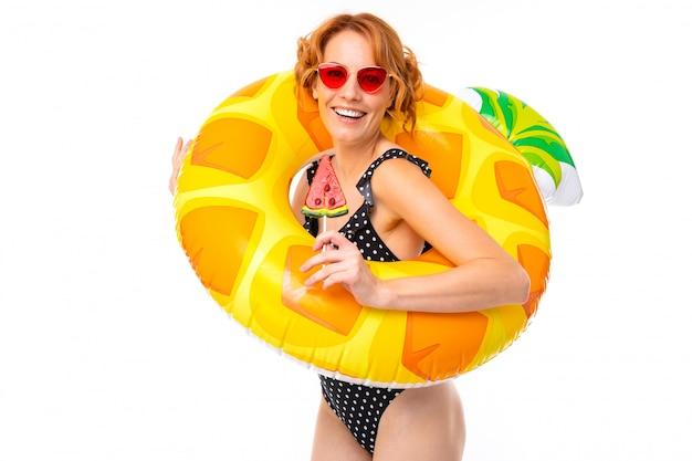Ragazza sexy in un costume da bagno in un cerchio di nuoto sotto forma di ananas in vacanza su un bianco