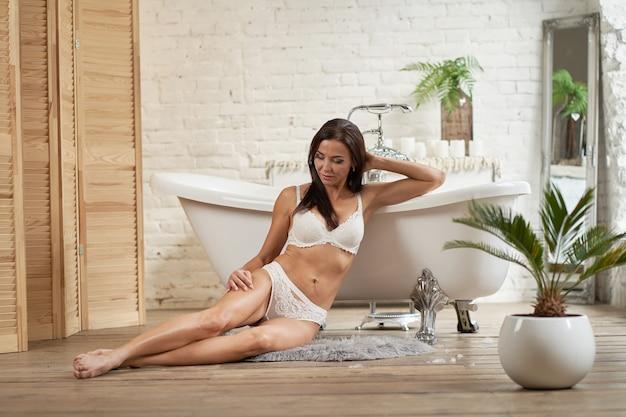 Ragazza sexy in biancheria intima che posa nel bagno vicino al bagno bianco.