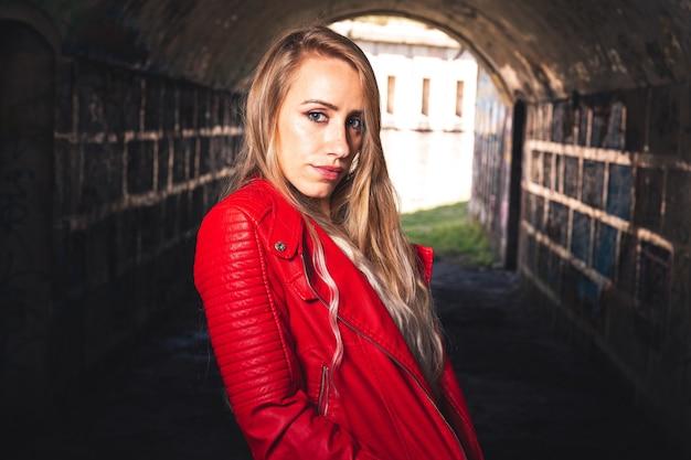 Ragazza sexy con una giacca rossa e un vestito bianco in un edificio in rovina