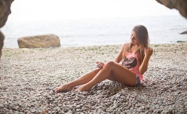 Sexy splendida giovane donna attraente sot sulla spiaggia fatta con piccole pietre. guarda in basso e mettiti in posa sulla fotocamera siediti vicino al mare o all'oceano. divertiti da solo. vacanze o vacanze.