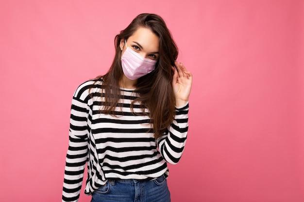 Sexy giovane donna attraente felice che indossa maschera facciale mediatica isolata sopra la parete di fondo. protezione contro il covid-19.