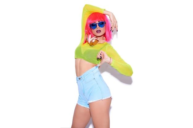 Dj ragazza sexy hipster indossando abiti luminosi colorati, parrucca rosa e cuffie su sfondo bianco