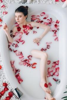 Signora sexy sdraiata nella vasca da bagno con schiuma e petali di rosa, vista dall'alto.