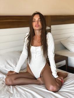 Signora sexy in tuta bianca in posa su un letto nella camera d'albergo