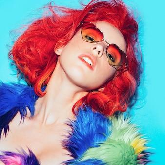Signora sexy con i capelli rossi nel cappotto luminoso, occhiali da sole cuori club style party