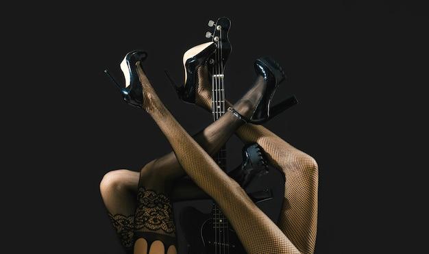 Gambe sexy. chitarra, chitarra elettrica. feticismo, donna sexy, chitarra elettrica e gambe, biancheria intima. biancheria fetish. festival di musica, musica dal vivo, concerto. strumento sul palco e banda. concetto di musica.
