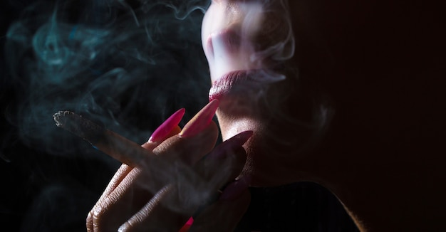Labbra sexy, bocca sensuale. labbra di sigaretta, fumo sexy. fumo di sigaretta, turbinio di fumo, movimento del fumo. macro della parte del viso della donna. primo piano, alta risoluzione.