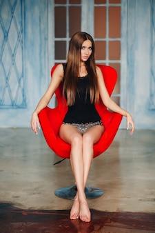 Donna dai capelli lunghi sexy che si siede nella sedia alla moda rossa.