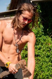 Giovane sexy dai capelli lunghi in occhiali da sole con il torso nudo che tiene un elicottero di legno.