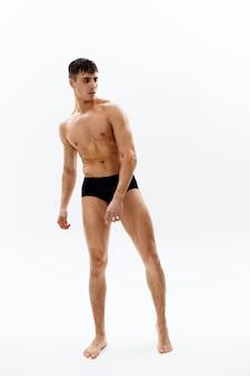 Culturista maschio sexy in pantaloncini scuri fitness sfondo chiaro