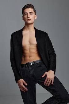 Un uomo sexy in una giacca abbottonata con un torso nudo tiene la mano vicino alla gamba