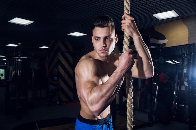Uomo sexy in palestra con manubri. uomo sportivo con grandi muscoli e un'ampia schiena si allena in palestra, fitness e pressa addominale pompata. russia, sverdlovsk, 2 giugno 2018