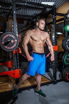 Uomo sexy in palestra con manubri. uomo sportivo con grandi muscoli e schiena ampia si allena in palestra, fitness e pressa addominale pompata