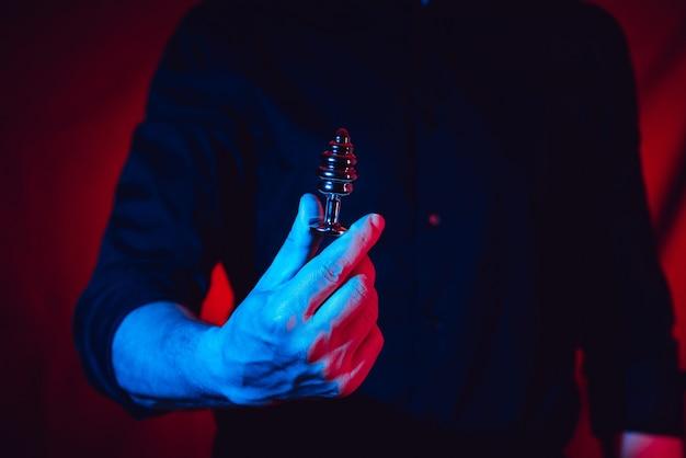 L'uomo sexy tiene in mano un plug anale bdsm. questo prodotto è solo per adulti