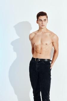 Uomo sexy con un torso nudo e pantaloni neri che tengono le mani dietro la schiena