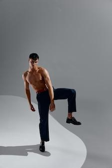 Uomo sexy con un torso nudo in jeans e scarpe su uno sfondo grigio con una gamba sollevata