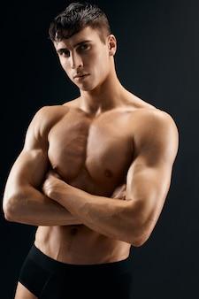 Uomo sexy con uno studio di sfondo scuro di atleta torso pompato