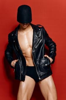 Uomo sexy con un torso pompato in mutandine nere e una giacca di pelle