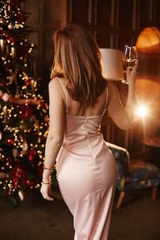 Modella sexy ragazza con un corpo perfetto, in un abito da sera con schiena nuda, tiene un bicchiere di champagne e posa con la schiena vicino all'albero di natale all'interno decorato per il nuovo anno.