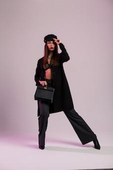 Giovane donna modello sexy in reggiseno di pizzo elegante in protezione in giacca in pantaloni stivali con borsa in pelle è in piedi nella stanza vicino al muro. bella ragazza castana che posa in vestiti neri alla moda all'interno.