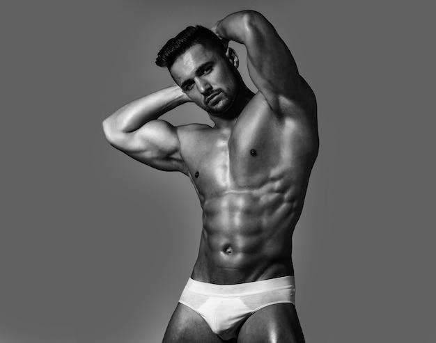 Corpo nudo forte del modello maschio muscoloso sexy uomo in mutandine bianche della biancheria intima