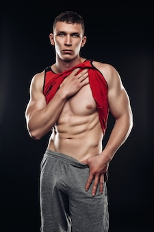 Uomo sexy fitness muscolare che mostra i muscoli sixpack senza grasso su sfondo nero. modello di fitness uomo atletico forte solleva la camicia e rivela un corpo muscoloso. sfondo nero dello studio.