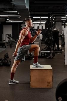 Uomini muscolosi sexy che usano la piattaforma per le gambe su uno sfondo colorato scuro della palestra.