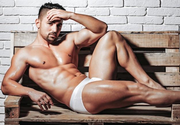 Uomini muscolosi sexy con il torso nudo corpo nudo in mutande sul divano pallet di legno