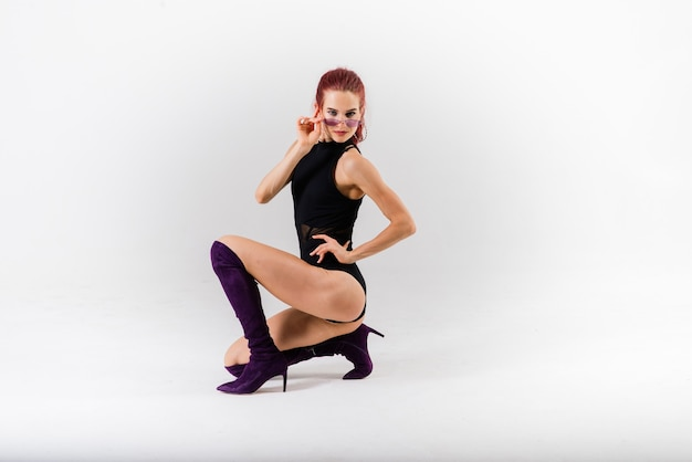 Ballerina sexy della testarossa del palo che mostra il suo corpo.